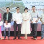 Bà Phạm Thị Hường trao sổ hồng cho khách hàng mua nhà đất tại dự án của công ty